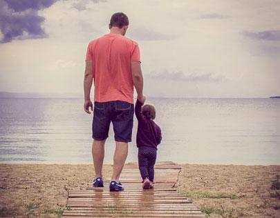 pappa med barn vid stranden